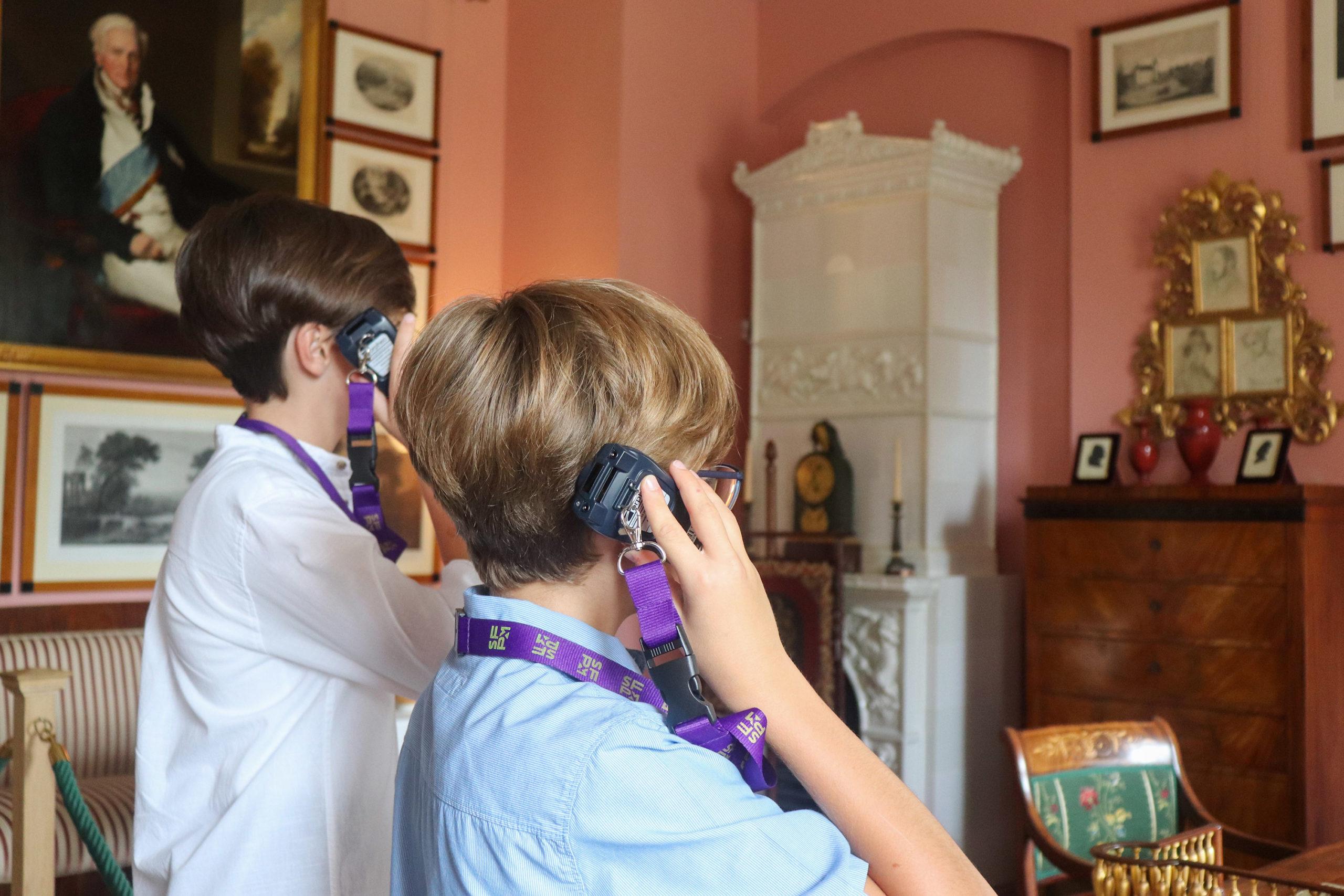Zwei Jungs mit einem Audioguide am Ohr schauen sich im Schloss Branitz die Kleine Saalstube der Fürstin Lucie von Pückler an und lauschen den Informationen des Audioguides