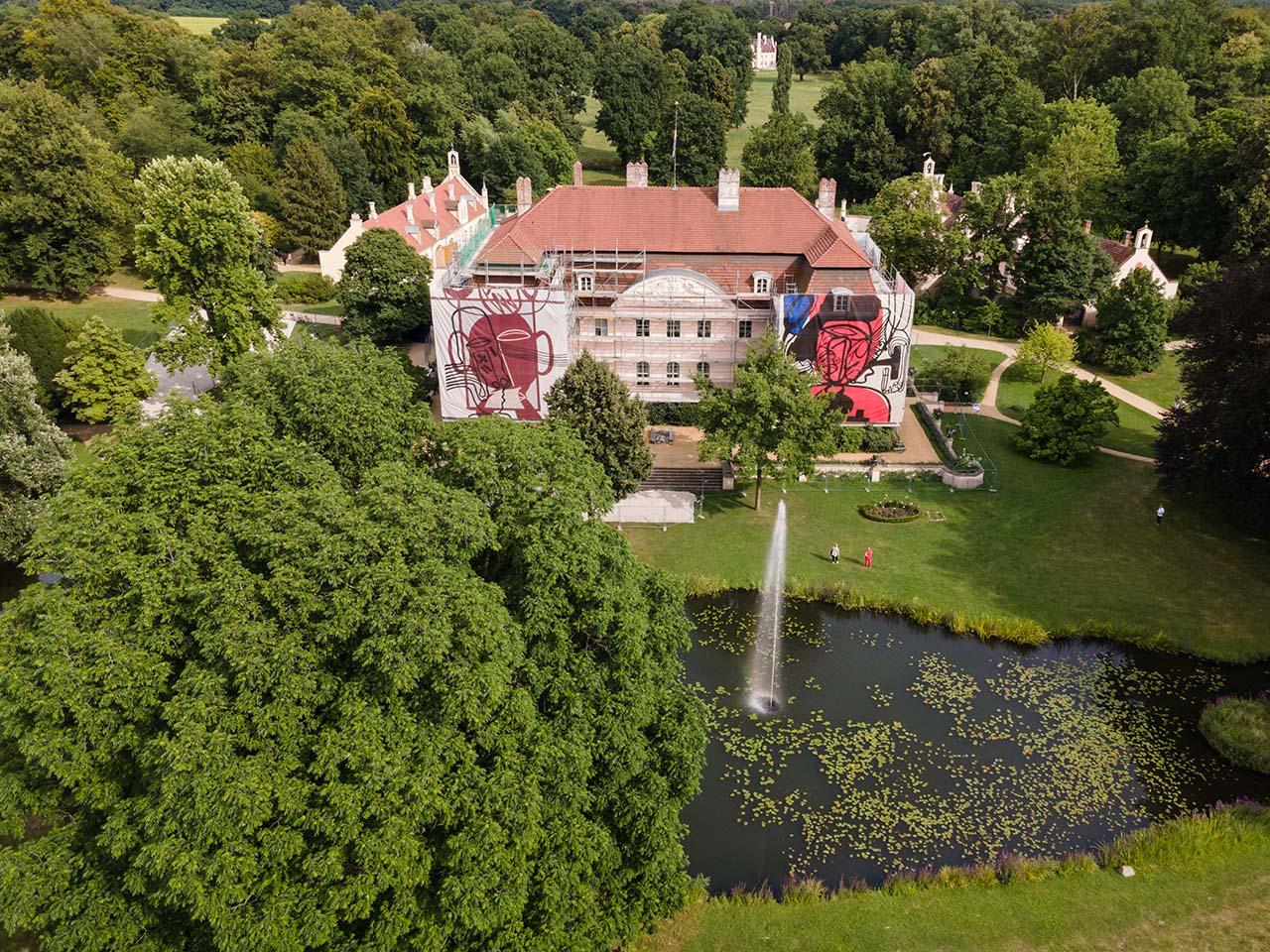 Luftbild vom Schloss Branitz mit Baugerüst. Am Baugerüst sind mehrere Planen mit Motiven des Künstlers Hans Scheuerecker angebracht